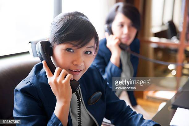 Asian female hotel concierges working at their desk
