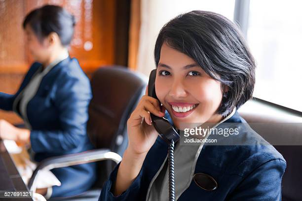 Asian female hotel concierges working at their desk  rm