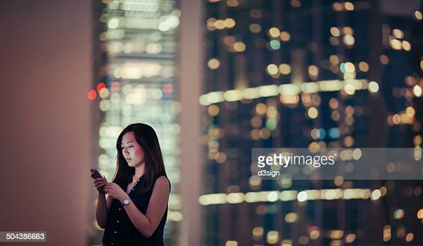 Asian female is using smartphone in city