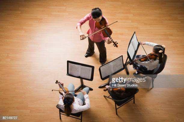 Asian female music teacher playing violin with class