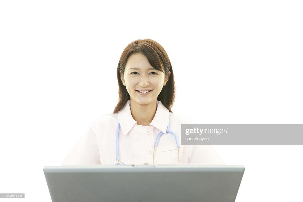 Asian female nurse with laptop computer : Stock Photo