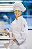 Asian female pastry chef holding piping bag