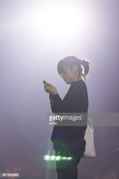 asian female playing cell phone under flood light