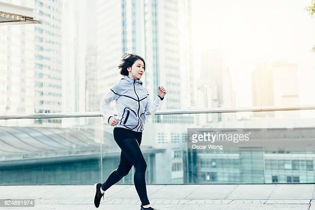 Asian female runner running on street