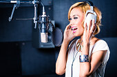 Asian professional female musician recording new song or album CD in studio
