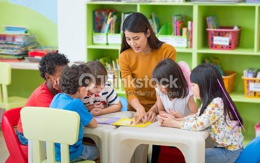 Asian female teacher teaching mixed race kids reading book in classroom,Kindergarten pre school concept. : Stock Photo