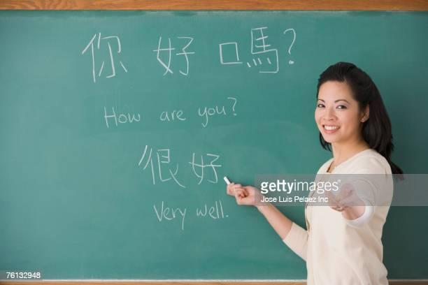 Asian female teacher writing Chinese on blackboard