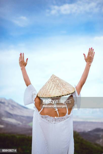 Asian Female wearing Traditional Straw Hat Praying with Raised Hands