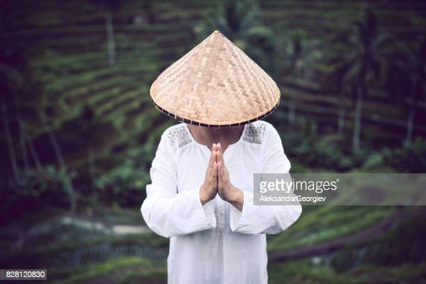 Asian Female with Traditional Straw how Praying at Rice Fields