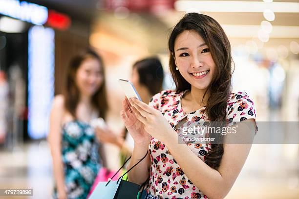 アジアのテキストメッセージによるご友人とのショッピングモールで
