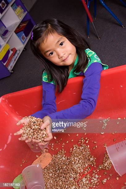 Asian girl at school sensory station