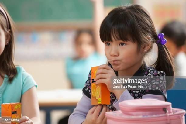 Asian girl drinking juice in classroom