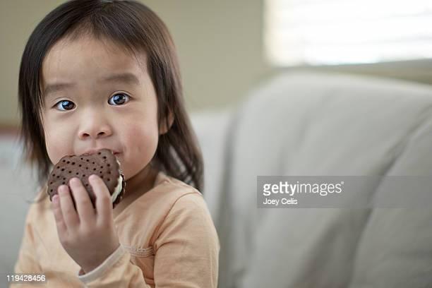 Asian girl eating an ice cream sandwich
