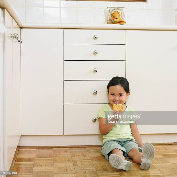 Asian girl eating cookie from jar