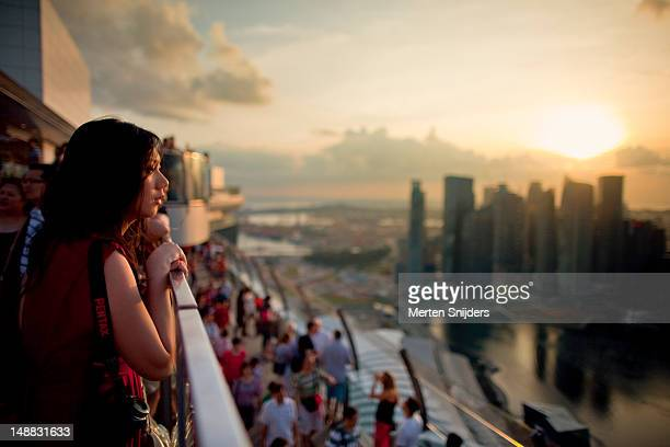 Asian girl enjoying the sunset from the rooftop of Marina Bay Sands.
