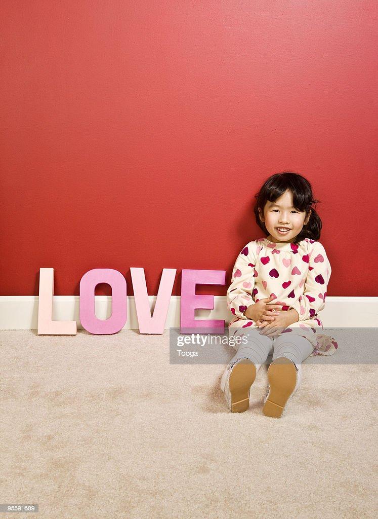Asian girl holding letters that spell 'LOVE' : Stock Photo