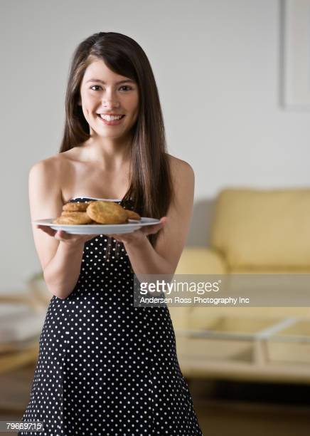 Asian girl holding plate of cookies