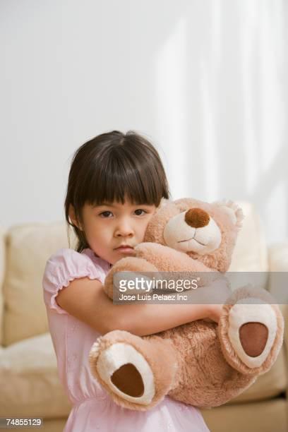 Asian girl hugging teddy bear