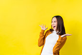Asian girl is surprised she is excited.Yellow background studio