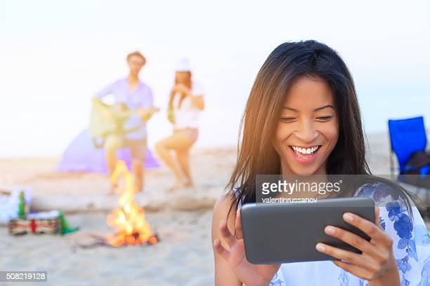 Asian girl looking digital tablet on the beach