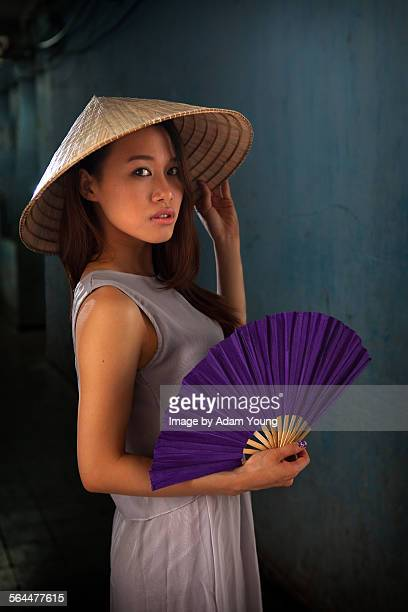 Asian girl looking to camera with non la and fan