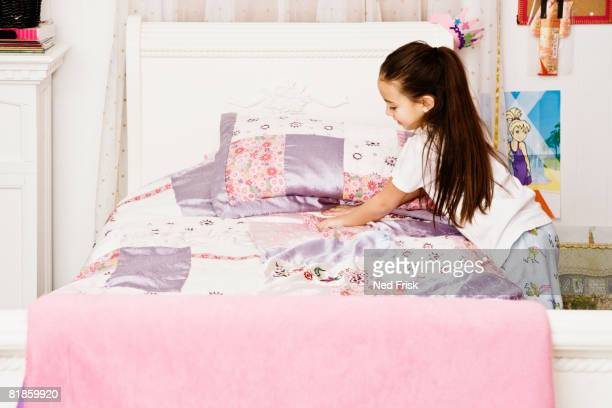 Asian girl making bed