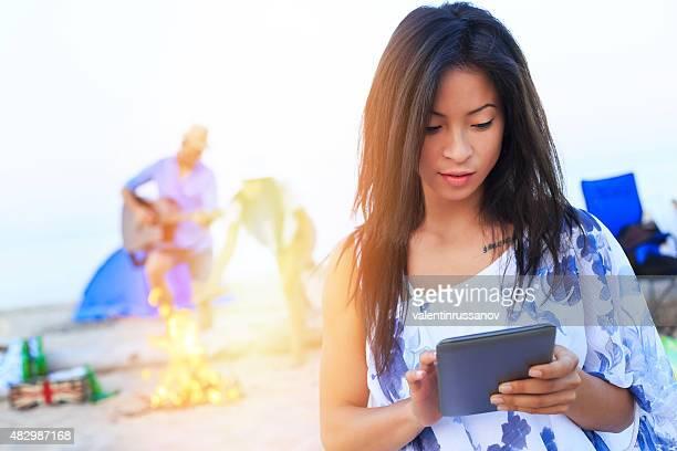 Asiatische Mädchen am Strand mit digital tablet