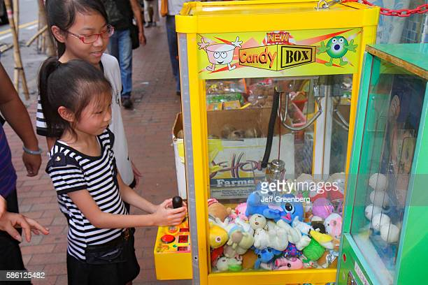 Asian girl playing carnival game claw prize stuffed animal