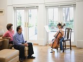 Asian girl playing cello for grandparents in livingroom