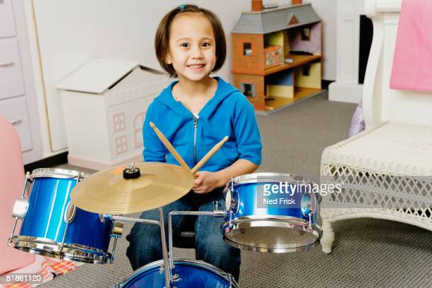 Asian girl playing drums