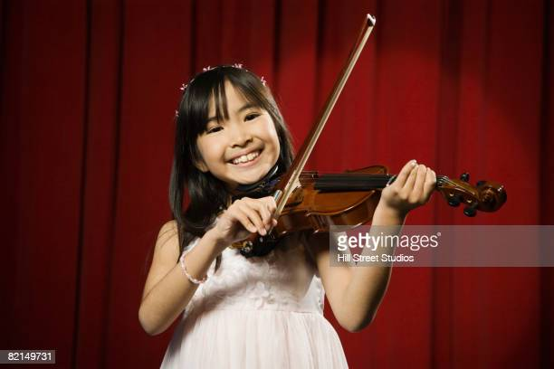 Asian girl playing violin on stage