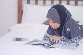 Asian girl reading at home