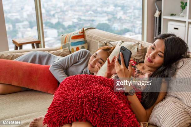 Asian Girl Relaxing on the Sofa With Her Phone