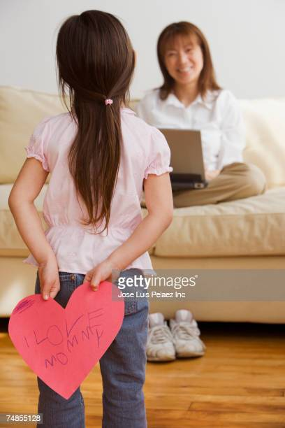 Asian girl surprising mother with paper cut out heart