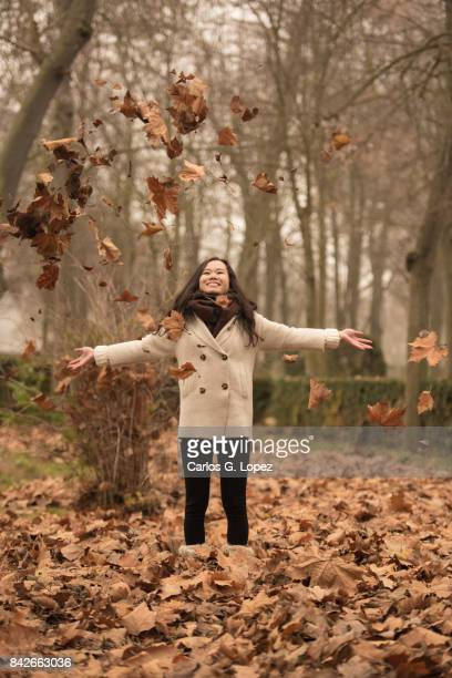 Asian girl throwing dry brown leaves up in the air while laughing