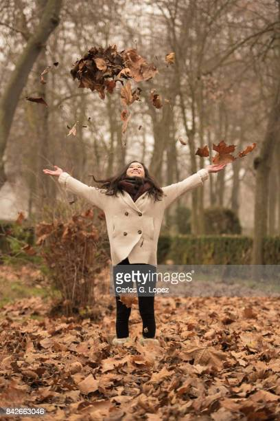 Asian girl throws dry brown leaves up in the air