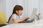 Asian girl typing on laptop