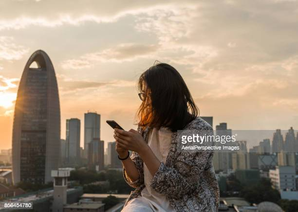 Asian Girl Using A Mobile Phone in Sunlight