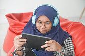 Asian girl using digital tablet at home
