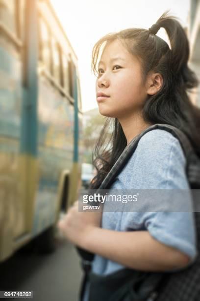 Asian girl waiting for bus on roadside.