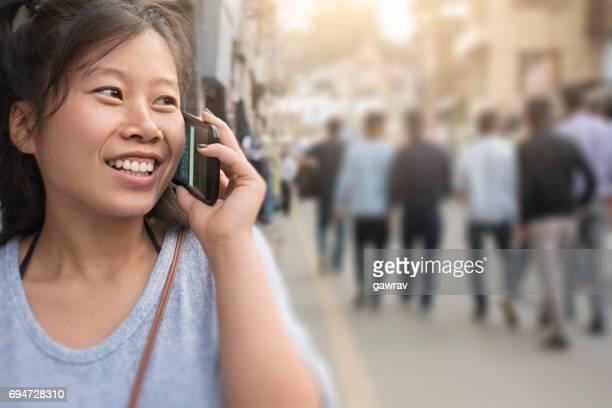 Asian girl walking on street while using smart phone.