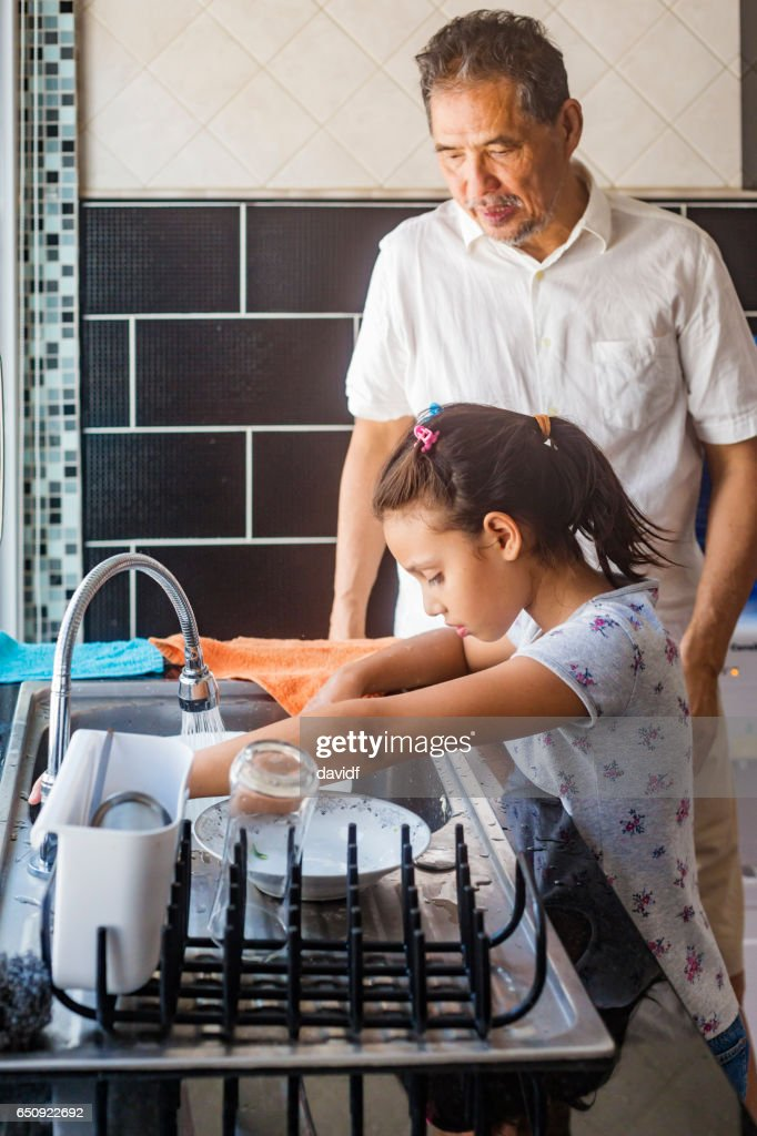 Asian Girl Washing Dishes While Grandfather Watches : Stock Photo