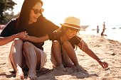 Asian girl wearing a hat and sunglasses and his mother sitting on the sand at the beach