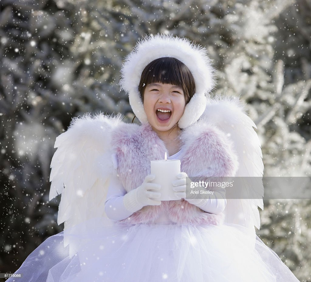 Asian girl wearing angel costume in snow