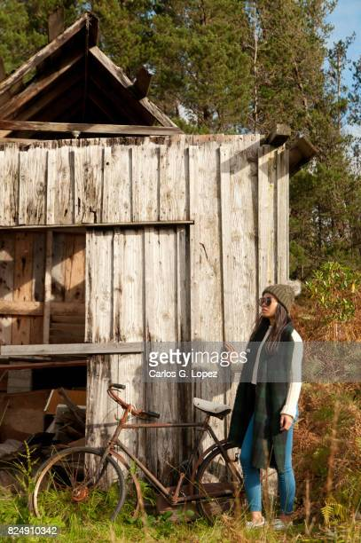 Asian girl wearing hat and scarf poses near old house in the field