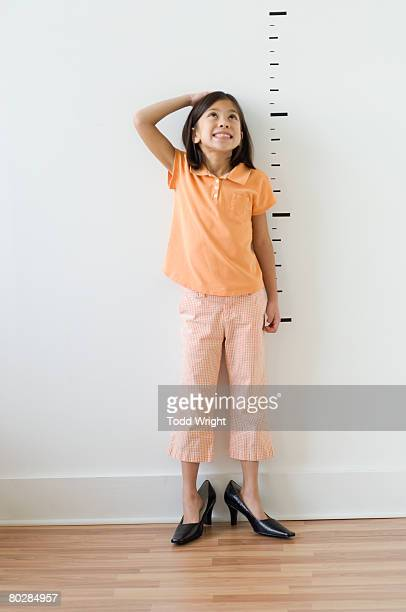 Asian girl wearing mother's shoes in front of height markers