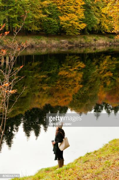 Asian girl wearing wooly hat stands near calm river with colorful reflections