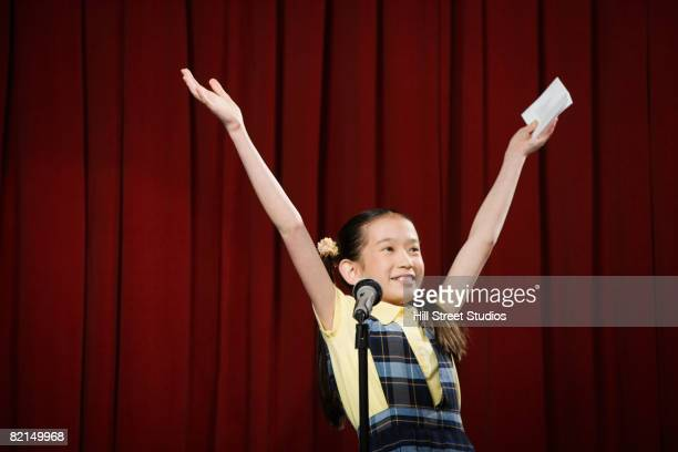 Asian girl with arms raised on stage
