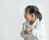 asian girl with big glass and science suite action on white screen. Funny  Action kid model with doctor or science costume.
