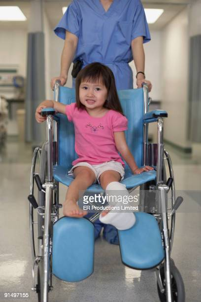 Asian girl with cast in wheelchair